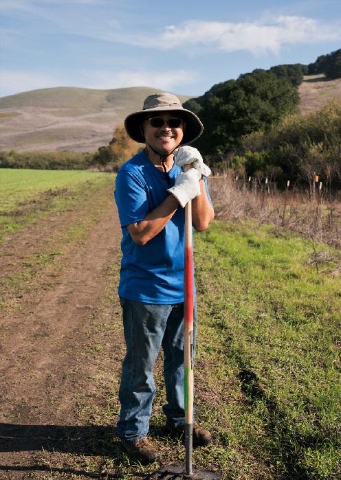 volunteer on trail holding rake
