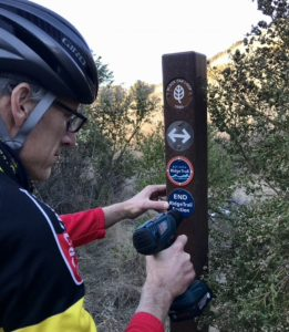 person installing ridge trail signs on sign post